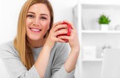 Una giovane donna sveglia sta tenendo una tazza rossa che si siede ad una tavola in un ufficio bianco Intervallo per il caffè Immagini Stock