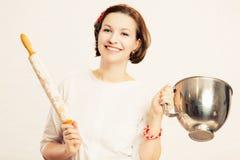 Una giovane donna tiene una ciotola da un miscelatore e un matterello in farina fotografie stock