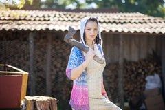 Una giovane donna tiene un'ascia Ritratto nel retro stile rurale fotografia stock libera da diritti
