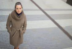 Una giovane donna in un cappotto beige cammina meditatamente giù la via immagine stock libera da diritti