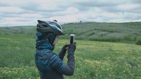 Una giovane donna in un casco prende le immagini della natura dello smartphone stock footage