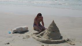 Una giovane donna in un costume da bagno con un cane bianco su una spiaggia abbandonata con un castello della sabbia costruito un video d archivio