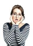 Una giovane donna in un maglione stretto a strisce, durante intorno ai vetri, fa un fronte spiacevole fotografie stock