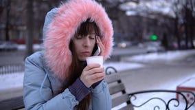 Una giovane donna in un rivestimento caldo grigio utilizza un telefono nella via nell'inverno archivi video