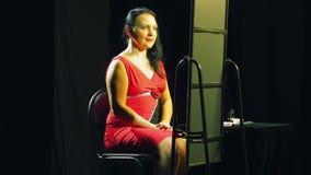 Una giovane donna in un vestito rosso con un trucco luminoso si pavoneggia davanti ad uno specchio stock footage