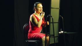 Una giovane donna in un vestito rosso davanti ad uno specchio applica il rossetto rosso luminoso sulle sue labbra stock footage