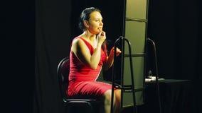 Una giovane donna in un vestito rosso davanti ad uno specchio mette un contorno rosso sulle sue labbra stock footage