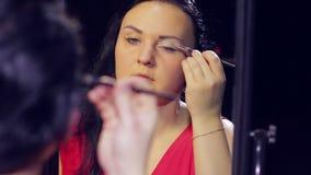 Una giovane donna in un vestito rosso davanti ad uno specchio mette l'ombra leggera sulle palpebre stock footage