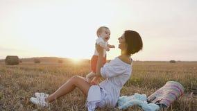 Una giovane donna in un vestito sta divertendosi il gioco con un ragazzino nel campo La mamma ed il figlio sono passeggiate nell'
