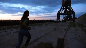 Una giovane donna in una tuta sportiva che pareggia lungo il pilastro della sabbia del porto del carico, nella penombra dell'alba archivi video