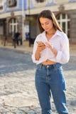 Una giovane donna, vestita nello stile casuale, scrive un messaggio franco immagini stock