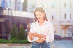 Una giovane donna, vestita nello stile casuale, scrive un messaggio per immagine stock