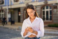 Una giovane donna, vestita nello stile casuale, scrive un messaggio per fotografia stock