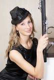 Una giovane donna in vestito nero ed in un cappello fotografia stock libera da diritti