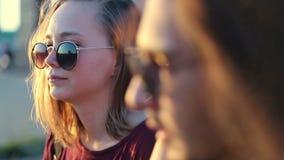 Una giovane donna in vetri - giovani coppie che parla l'un l'altro all'aperto archivi video