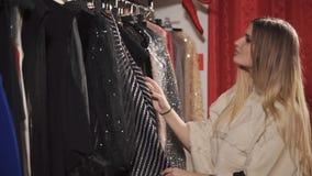 Una giovane e donna graziosa era interessata in vestiti brillanti per un evento di sera video d archivio