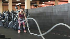 Una giovane e ragazza atletica attraente che usando l'addestramento ropes in una palestra video d archivio