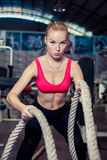 Una giovane e ragazza atletica attraente che usando l'addestramento ropes in una palestra Immagine Stock