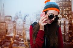 Una giovane e ragazza positiva con gli occhiali da sole sta parlando sul telefono nella sua stanza contro lo sfondo della città Fotografie Stock Libere da Diritti