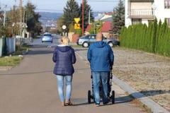 Una giovane famiglia cammina lungo le vie della cittadina Il marito e la moglie stanno camminando con il bambino Il padre spinge  immagini stock