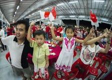 Una giovane famiglia canta uno della canzone di festa nazionale ed ondeggia le mini bandiere nazionali con orgoglio e la gioia Fotografie Stock