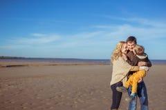 Una giovane famiglia che bacia e che abbraccia alla spiaggia Immagine Stock