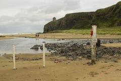Una giovane famiglia che passeggia attraverso la spiaggia in discesa in contea Londonderry in Irlanda del Nord con il tempio di M immagini stock