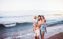 Una giovane famiglia con due bambini del bambino che stanno sulla spiaggia sulla vacanza estiva immagine stock libera da diritti