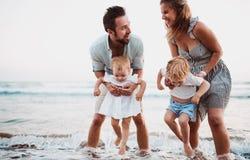 Una giovane famiglia con due bambini del bambino divertendosi sulla spiaggia sulla vacanza estiva fotografie stock