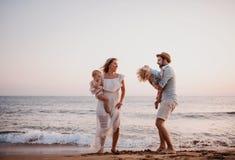 Una giovane famiglia con due bambini del bambino divertendosi sulla spiaggia sulla vacanza estiva immagini stock