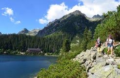 Una giovane famiglia con il bambino in un'imbracatura che fa un'escursione vicino al lago della montagna di Popradske Pleso in al Fotografia Stock
