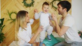 Una giovane famiglia con il piccolo gioco del figlio sul letto nella camera da letto immagine stock libera da diritti