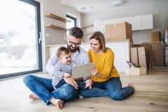 Una giovane famiglia con una ragazza del bambino che si muove nella nuova casa, facendo uso della compressa fotografia stock
