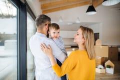 Una giovane famiglia con una ragazza del bambino che si muove nella nuova casa fotografia stock