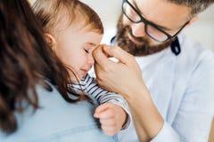 Una giovane famiglia con una ragazza gridante del bambino che sta all'interno a casa, midsection fotografia stock