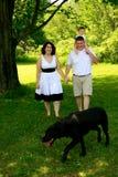 Una giovane famiglia di tre che cammina con il cane Immagine Stock Libera da Diritti