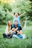 Una giovane famiglia di tre felice divertendosi insieme all'aperto Figlia abbastanza piccola sulla sua parte posteriore del padre Fotografia Stock Libera da Diritti