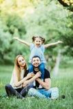 Una giovane famiglia di tre felice divertendosi insieme all'aperto La figlia abbastanza piccola sul suo a due vie del padre che s Fotografia Stock