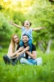 Una giovane famiglia di tre felice divertendosi insieme all'aperto La figlia abbastanza piccola sul suo a due vie del padre che s Immagine Stock
