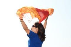 Una giovane femmina nel flusso continuo del chiffon arancio su fondo bianco. fotografie stock