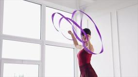 Una giovane ginnasta è formata per ballare con un nastro che fluttua nell'aria stock footage