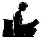 Una giovane lettura caucasica del ragazzo o della ragazza della siluetta dell'adolescente Immagine Stock
