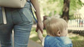 Una giovane madre cammina con il suo giovane figlio all'aperto La donna sta tenendo il ragazzo dalla mano video d archivio
