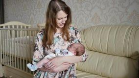 Una giovane madre che oscilla un bambino lei armi stock footage