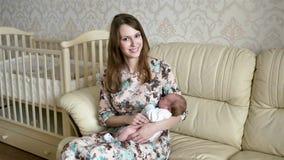 Una giovane madre che oscilla un bambino lei armi archivi video