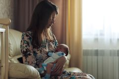 Una giovane madre che oscilla un bambino lei armi immagine stock libera da diritti