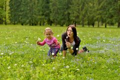 Una giovane madre con una piccola figlia che gioca su un prato verde fotografia stock libera da diritti