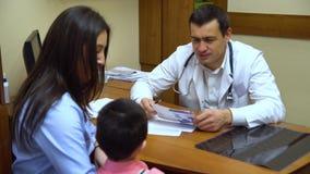 Una giovane madre con un bambino al medico stock footage