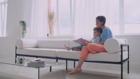 Una giovane madre con un bambino che legge un libro che si siede in un interno bianco luminoso della casa nel salone sul archivi video