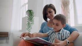 Una giovane madre con un bambino che legge un libro che si siede in un interno bianco luminoso della casa nel salone sul stock footage